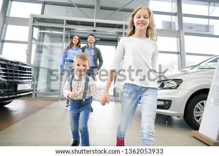 Front view of funny little boy with elder sister entering in big auto showroom. Cute children with parents looking at new cars, choosing and testing automobiles. Concept of car buying. #1362053933