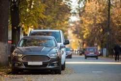 Front view of gray expensive luxurious car parked in quiet alley on sunny autumn day on blurred vehicles, walking people and golden foliage bokeh background. Transportation, parking problems concept.