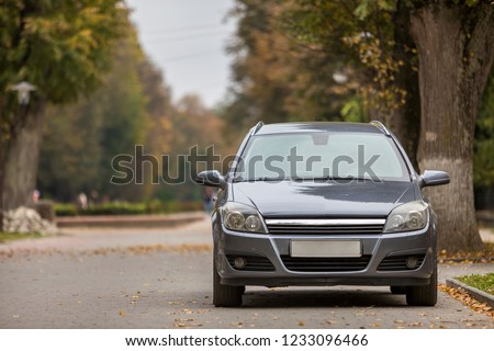 Front view of gray shiny empty car parked in quiet area on wide alley under big trees on blurred green and yellow folliage bokeh background on bright sunny day. Transportation and parking concept.