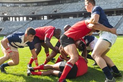Front view of group of diverse male rugby players playing rugby match in stadium. Players tackling each other down.