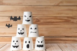 Front view of Halloween crafts, paper cup ghost on wooden wall background and black bat background with copy space for text. Halloween concept.