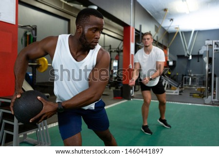 Front view of handsome diverse male athletics exercising together with exercise ball in fitness center. Bright modern gym with fit healthy people working out and training