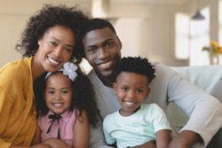 Front view of happy African American family sitting on sofa and looking at camera in a comfortable home. Social distancing and self isolation in quarantine lockdown for Coronavirus Covid19