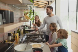 Front view of happy Caucasian family preparing food in kitchen in a comfortable home