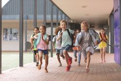 Front view of happy diverse school kids running in corridor at school