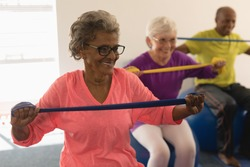 Front view of happy diverse senior woman exercising with resistance band in fitness studio