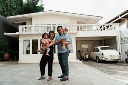 Front view of happy family take a photo infront of the house.