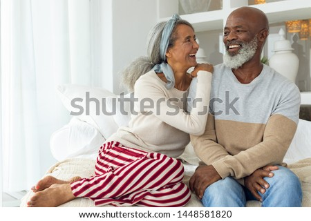 Front view of happy senior diverse couple sitting in a white room on beach house. Authentic Senior Retired Life Concept