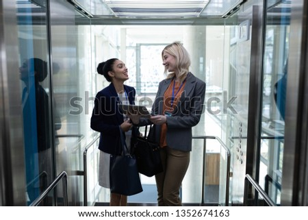 Front view of happy young multi-ethnic businesswomen discussing over digital tablet in modern office elevator. They are smiling #1352674163