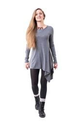 Front view of happy young stylish woman in gray tunic walking towards camera. Full body isolated on white background.
