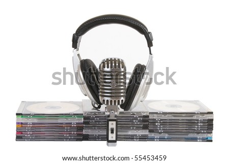 Front view of headphones, vintage microphone, cd, dvd stack