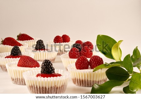 Front view of homemade cheesecakes and homemade strawberry sauce accompanied by strawberries, blackberries, raspberries and green leaves on white background.