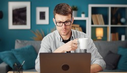 Front view of involved young man browsing laptop and holding cup sitting at table in living room