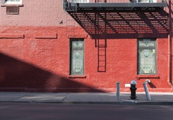 Front view of iron fire escape stair in red and pink/ purple brick building with hydrant an copyspace