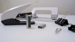 Front view of isolated office equipment: stapler, paper hole punch, binder clips (or fold back clips office) and paper clips in white background, focused on paper clip.