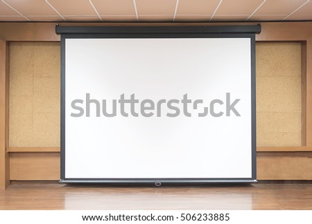 Front view of lecture room with empty white projector screen