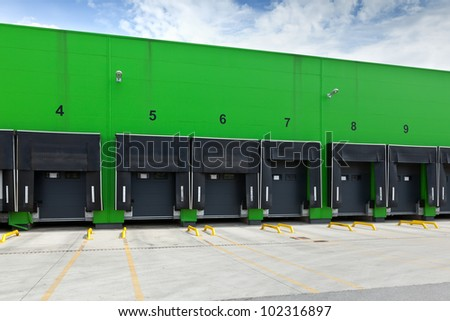 Front view of loading docks in the industrial warehouse with green wall and enumerated black doors