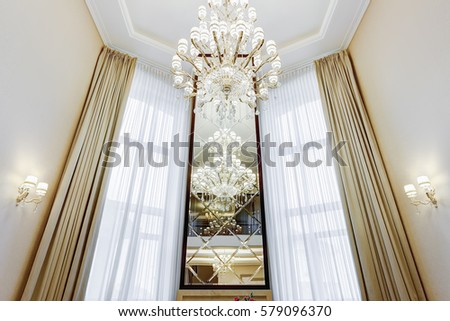 Front view of long mirror between windows with luxury curtains. Interior in brown, beige colors. Room with big windows, beige wall and crystal chandelier of center of ceiling.