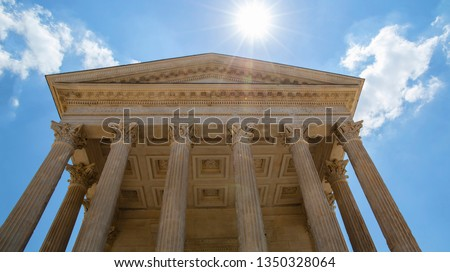 Front view of Maison Carree (square house), ancient building in Nimes, France, one of the best preserved antique Roman temple facades, low angle