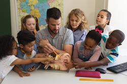 Front view of male Caucasian teacher explaining anatomy using anatomical model at desk with students who listen carefully in classroom of elementary school