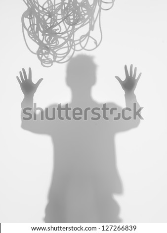 front view of man holding his hands up, wanting to break free, with tangled rope on top of his head, behid a diffuse surface - stock photo