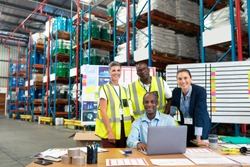 Front view of mature African-american male supervisor with his diverse coworkers discussing over laptop at desk in warehouse. This is a freight transportation and distribution warehouse. Industrial