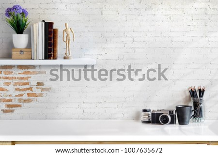 Front view of minimal desk and designer tools over white brick wall. copy space for product display montage. #1007635672