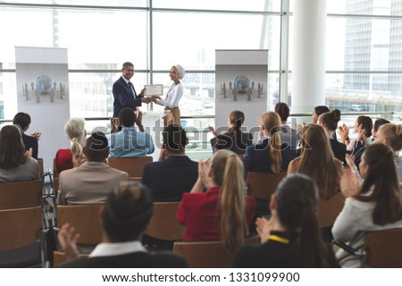 Front view of mixed race businesswoman receiving award from mixed race businessman in front of business professionals applauding at business seminar in office building