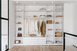 Front view of modern and large wardrobe in dressing room with fashionable woman clothes wear, shoes and bag