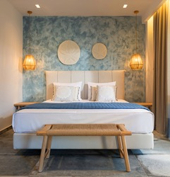 Front view of modern bedroom interior in nautical marine style with blue decorative stucco wall, wicker furniture, ceiling wooden lamps, white soft bed