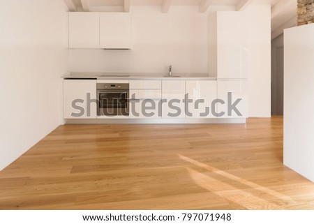 Front view of modern kitchen. Parquet floor and wooden beams
