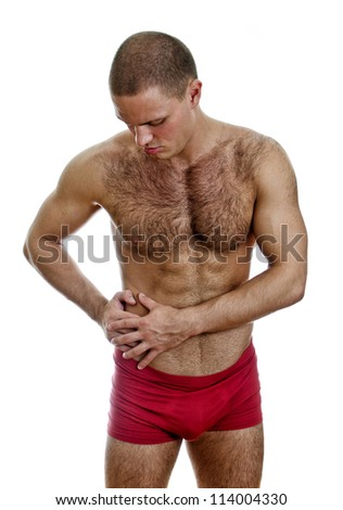 Front view of muscular man suffering from stomach pain. Isolated on white.