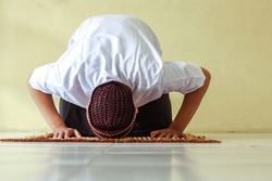 Front view of muslim man doing Salat with prostration pose on the prayer mat