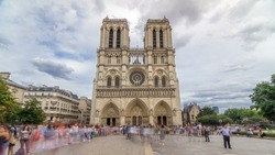 Front view of Notre-Dame de Paris timelapse  is a medieval Catholic cathedral on the Cite Island in Paris, France. Long queue of tourists. Cloudy sky at summer day