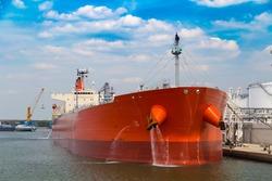 Front view of oil tanker moored near oil silo in Port of Antwerp, Belgium