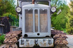 Front view of old crawler tractor. Detailed view of tractor. Soviet gray crawler. Nature landscape background. Front-bottom view.