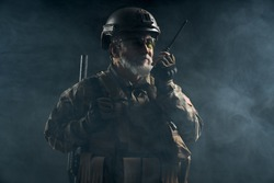Front view of old military soldier in uniform holding portable radio station in smoke. Close up of male commander in camouflage uniform giving orders in dark atmosphere. Concept of army, military.