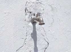 Front view of old nickel faucet on uncorked white concrete wall. Hardware and plumbing. Detail of drip water faucet, garden taps. Save water concept. Close up, selective focus.