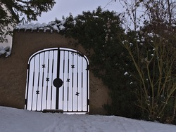 Front view of old stone wall with iron gate and decorated lattice on cloudy winter day with snow-covered path, climbing plant and bare bush near Wurmlingen, Germany.