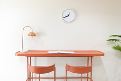 front view of orange study desk or workplace with metal electrical table lamp and white minimalist clock without numbers hanging on the wall