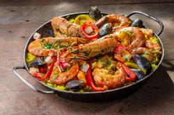 Front view of paella Spanish dish, served in the pan on a rustic wooden table , shrimp, lobster, mussels, rice, red pepper and spices