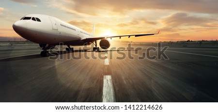 Front view of parked commercial airplane on runway. Modern and fastest mode of transportation. Dramatic sunset sky on background