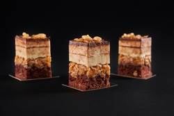Front view of pieces of fresh dessert layered with biscuit and mousse isolated on black background. Closeup view of three square slices of sweet brown chocolate cake with glazed top and nuts.