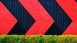 Front view of red arrows pattern on black corrugated metal wall behind green bush fence in exterior architecture decorations design concept