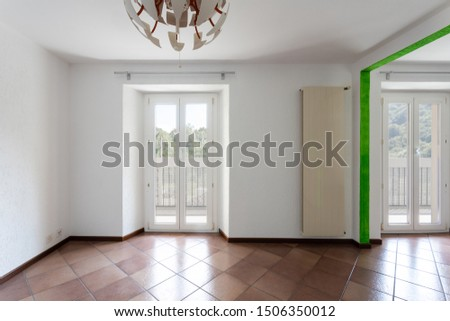 Front view of room with white walls and window looking nature. Nobody inside
