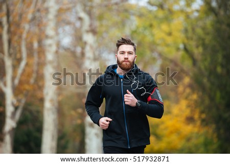 Front view of runner in park. looking at camera