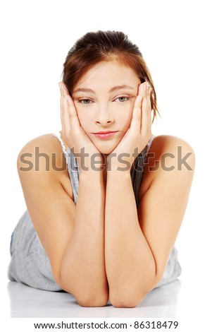 Front view of sad teen girl lying on her tummy, on white background