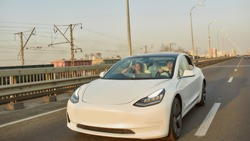 Front view of sedan electric car with driver and passenger moving along aspalted city road in sunlights, widescreen. Luxury and success concept