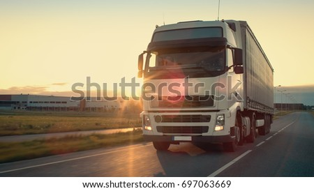 Front-View of Semi-Truck with Cargo Trailer Driving on a Highway. He's Speeding Through Industrial Warehouse Area with Sunset in the Background.