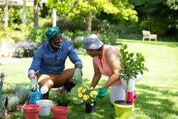 Front view of senior African American couple in the garden, gardening and talking. Family enjoying time at home, lifestyle concept